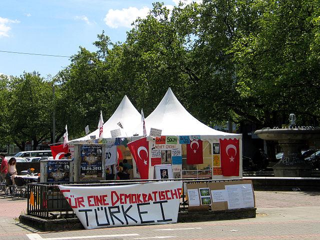"""By Bernd Schwabe in Hannover (Own work) [CC-BY-3.0 (http://creativecommons.org/licenses/by/3.0)], via Wikimedia Commons"""" Transparent Für eine demokratische Türkei vor den Zelten der Mahnwache am Klagesmarkt Hannover"""""""